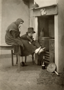 A vintage photograph of two people warming their feet next to a home heating system