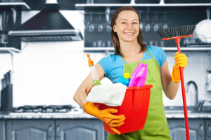 A woman holding cleaning supplies