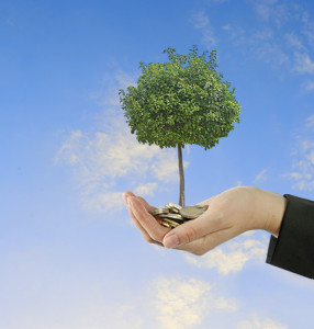 Image of a hand holding a tree and coins signifying efficient air conditioning