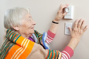 Woman Adjusting Her Minneapolis Furnace Thermostat