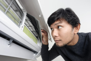 A man looking at his air conditioner and considering air conditioning repair