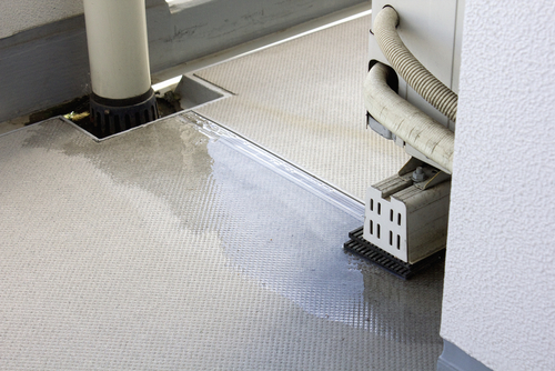 An air conditioner leaking condensation onto the floor