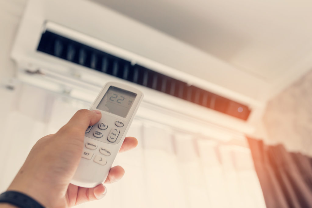 Person Operating a Ductless Air Conditioner With a Remote Control
