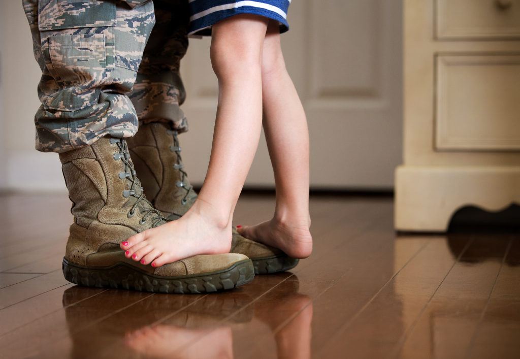 Child Dancing on Military Dad's Feet at Home