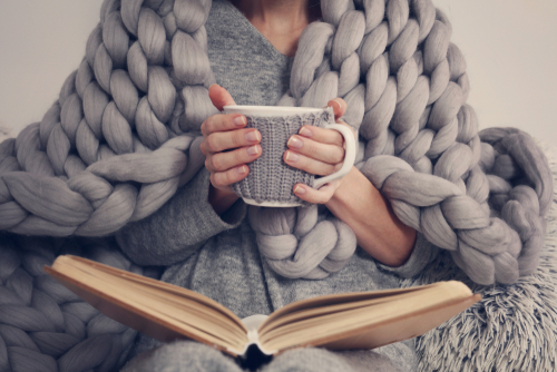 Woman Staying Warm With a Throw Blanket