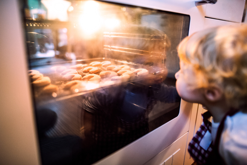 Child Watching Cookies Bake in Oven