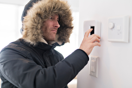 Man in a Winter Coat Checking the Thermostat