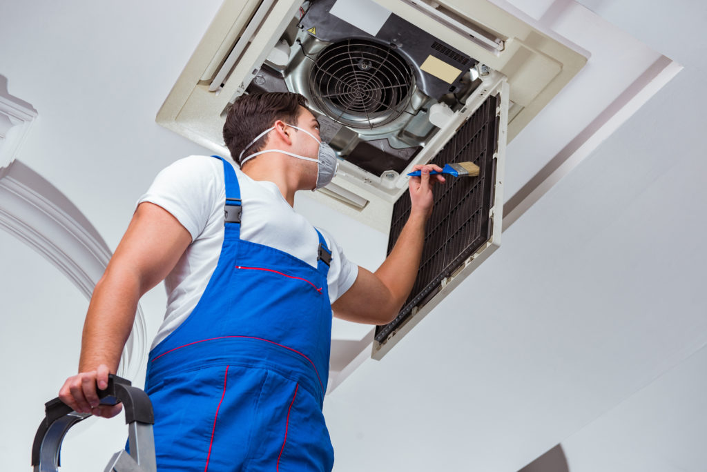 Air Conditioning Technician Safely Cleaning AC Unit