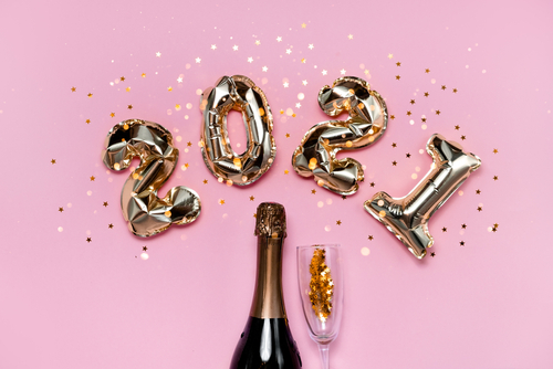 Gold Balloons Spelling 2021 in Front of Pink Background