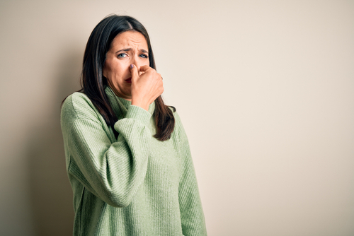 Woman Holding Her Nose to Block a Bad Smell