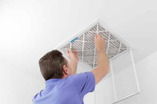 Man Changing an Air Filter on Home Ceiling Vent