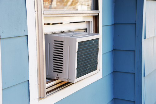 Traditional Window Air Conditioning Unit Installed in Window of Blue Home