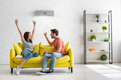 Couple on Yellow Couch in Room with Air Conditioner on Wall