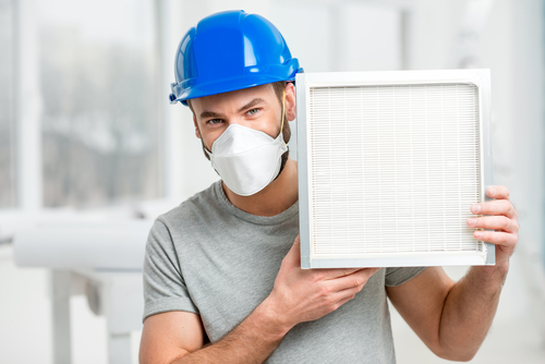 Man in Blue Hard Hat Holding Clean Air Filter